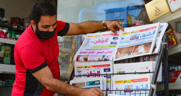 A shop owner arranges newspapers on a newsstand in the Qatari capital Doha showing headlines about the outcome of the GCC summit held in the Saudi desert city of Al-Ula. (AFP)