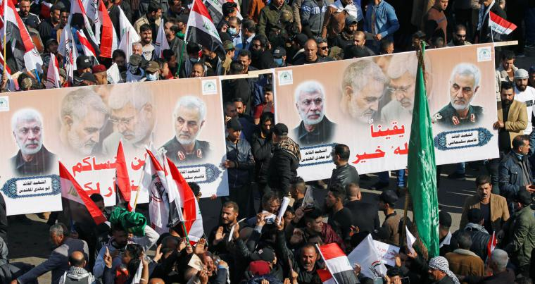 Iraqis, including supporters of the Popular Mobilisation Forces hold pictures of General Qassem Soleimani and commander Abu Mahdi al-Muhandis, as they mark the one year anniversary of their killing, in Baghdad, Iraq, January 3, 2021. (Reuters)