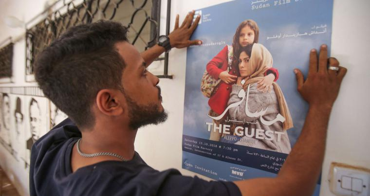 "Ahmad Faysal, Logistics manager of the ""Sudan Film Factory"", looks at film poster. (AFP)"