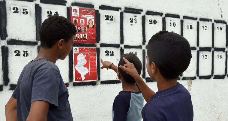 A file picture shows Tunisian youth looking at election posters put up on a streeet in Tunis. (AFP)