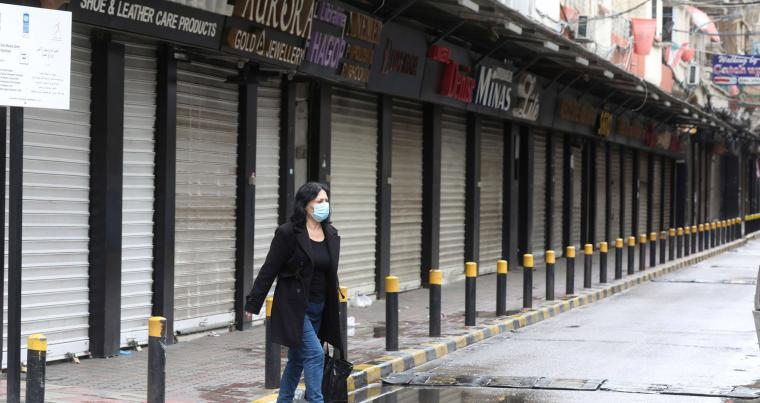A woman wearing a face mask walks along a street, as Lebanon tightened its lockdown and introduced a 24-hour curfew to curb the spread the coronavirus disease (COVID-19) in Beirut, Lebanon, January 14, 2021. (Reuters)