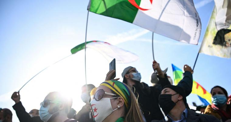 Demonstrators wave Algerian national flags during a rally in Paris on February 21, 2021, in support of the Hirak anti-government movement in Algeria. AFP