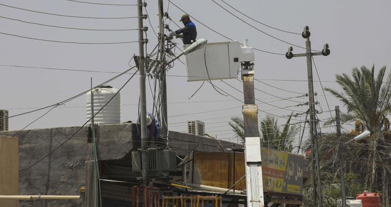 Ministry of electricity workers work to maintain the electricity network in Basra, Iraq. (AP)