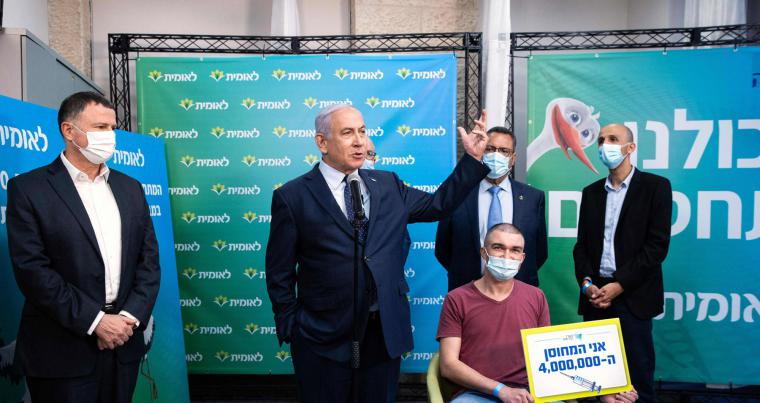 Israeli Prime Minister Netanyahu (2nd L) and Health Minister Yuli Edelstein (L) stand by the 4,000,000th person to be vaccinated, in Jerusalem on February 16, 2021. AFP