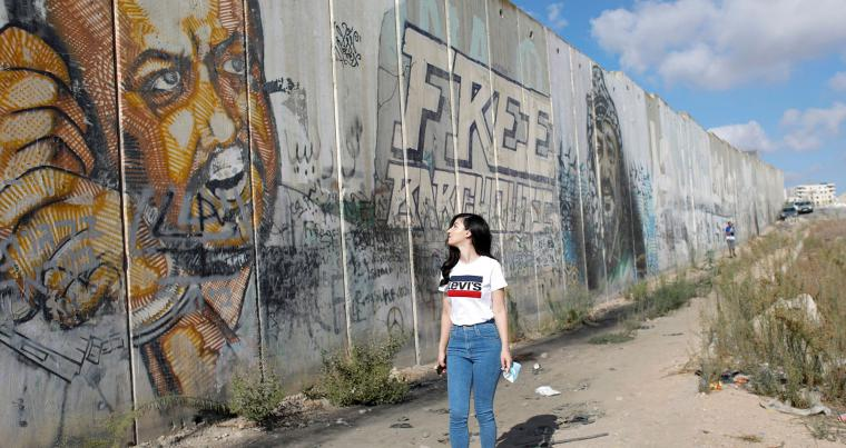 A young Palestinian woman looks at a mural depicting jailed Fatah leader Marwan Barghouti near Ramallah in the Israeli-occupied West Bank. (Reuters)