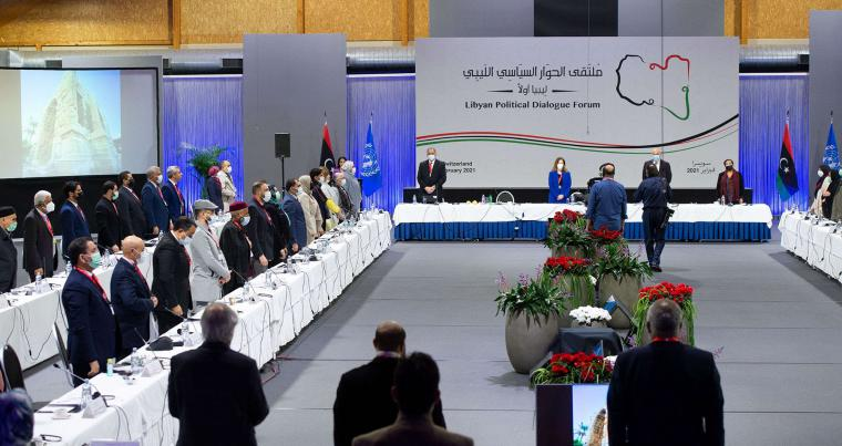 Libyan delegates stand during the national anthem at the opening of the Libyan Political Dialogue Forum on February 1, 2021 at an undisclosed location near Geneva to choose a new temporary executive authorities. (AFP)