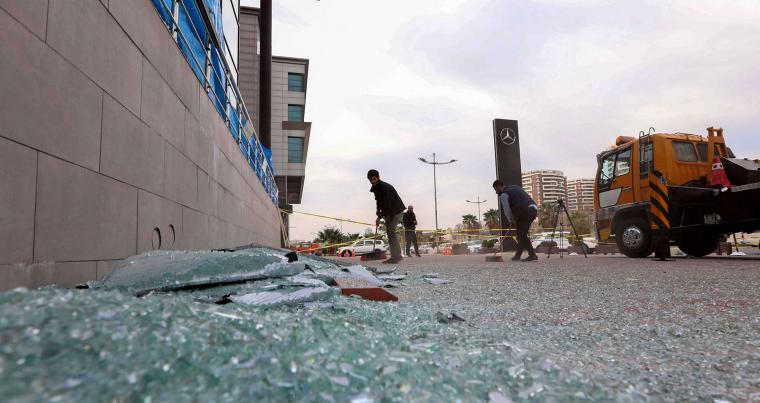 A worker cleans shattered glass on February 16, 2021 outside a damaged shop following a rocket attack the previous night in Erbil, the capital of the northern Iraqi Kurdish autonomous region. (AFP)