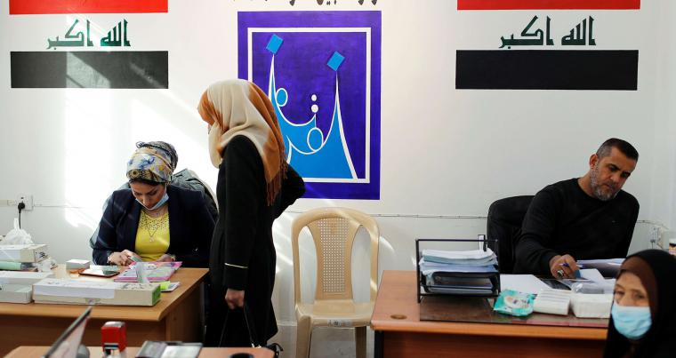 An Iraqi woman receives her new voter ID at an Independent High Electoral Commission centre in Baghdad, Iraq January 20, 2021. (Reuters)
