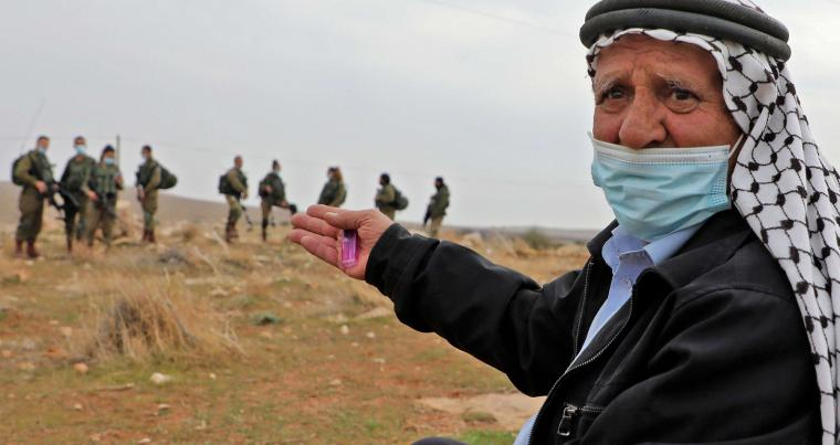 Israeli soldiers stand guard as an elderly Palestinian man gestures during a protest against the prevention of Palestinian farmers from ploughing their lands seized by Jewish settlers, in the village of Aqraba, east of Nablus in the occupied-West Bank. (AFP)
