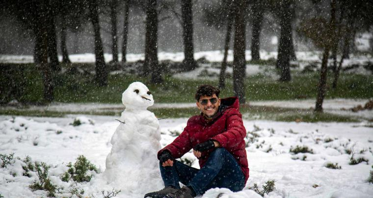 A Libyan man sits next to a snowman outside a forested area in the Sidi al-Hamri region of Libya's eastern Jebel Akhdar upland region, about 200 kilometres east of Benghazi. (AFP)
