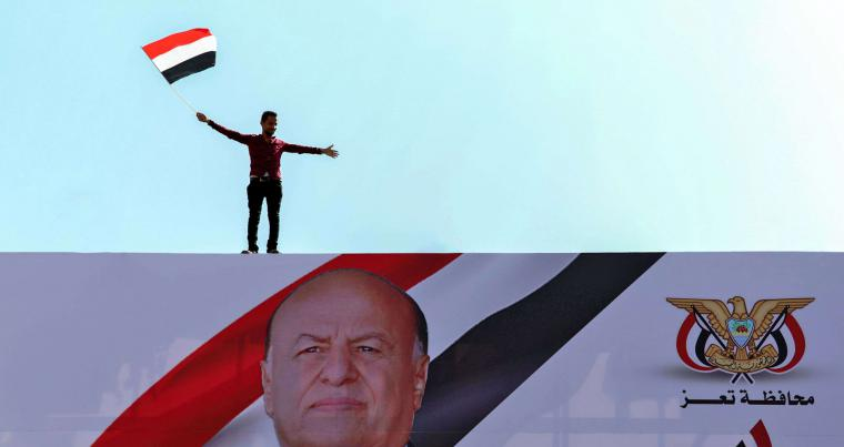 A Yemeni youth waves a national flag atop a billboard showing Yemen's President Abedrabbo Mansour Hadi during a rally commemorating the 10th anniversary of 2011 Arab Spring uprising, in Yemen's third city of Taez on February 11, 2021. (AFP)