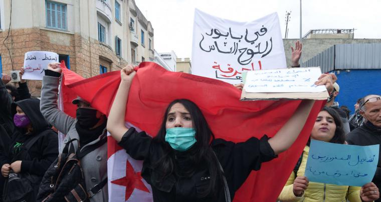 A Tunisian protester lifts a national flag during an anti-government demonstration in the capital Tunis. (AFP)