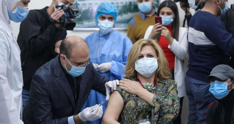 Lebanon's caretaker health minister Hamad Hassan administers a dose of the COVID-19 Pfizer/BioNTech vaccine to a member of the medical staff at the Rafik Hariri Hospital in the capital Beirut, on February 14, 2021. (AFP)