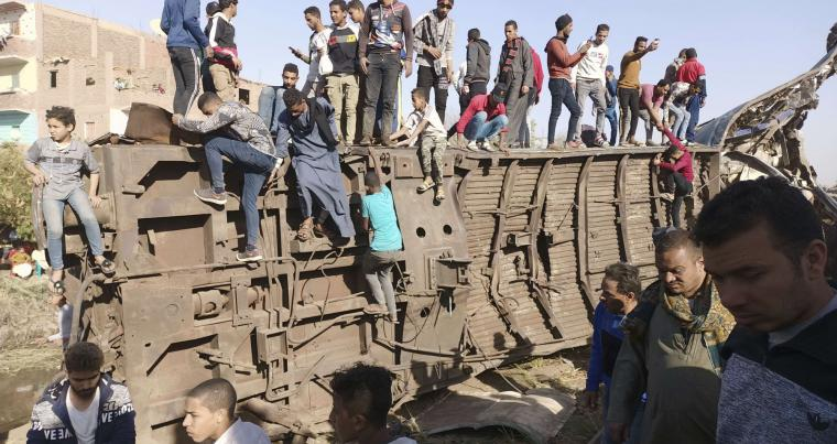 Egyptians gather around mangled train carriages at the scene of a train accident in Sohag, Egypt, March 26, 2021. AP