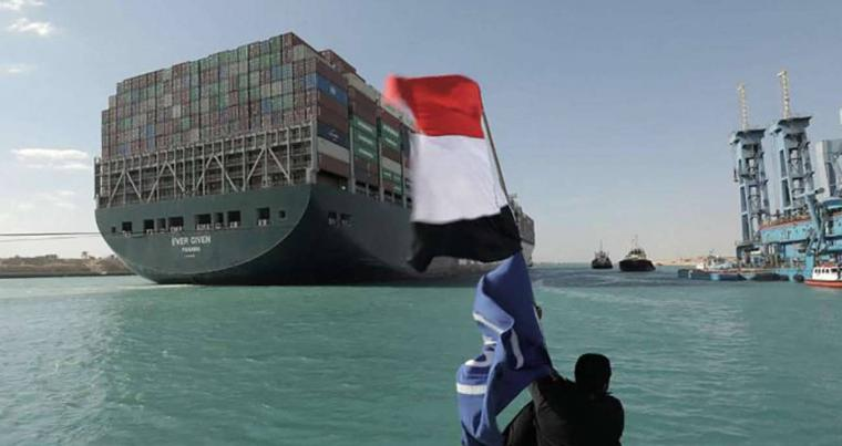 An Egyptian waves the national flag after Panama-flagged MV 'Ever Given' container ship was fully dislodged from the banks of the Suez, March 29, 2021.(REUTERS)