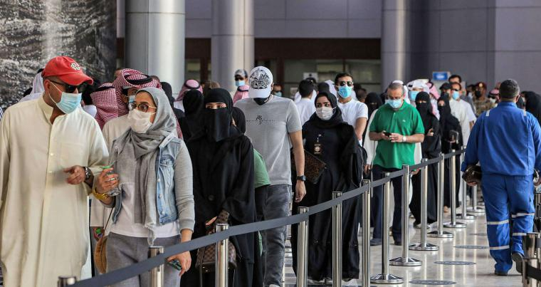 People wait their turn to receive a dose of coronavirus vaccine at the make-shift vaccination centre at the Kuwait International Fairground, south of Kuwait City. (AFP)