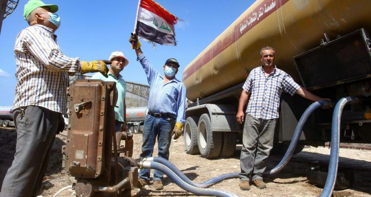 A worker raises an Iraqi national flag as a tanker truck filled with fuel offered by Iraq empties its content at the oil refinery of Zahrani, near the southerm Lebanese city of Sidon on August 20, 2020. (AFP)