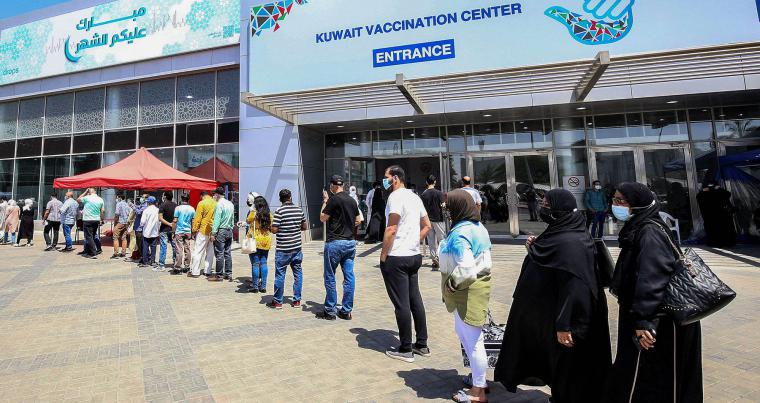 People queue as they wait their turn to receive a dose of a vaccine against the coronavirus at the Kuwait International Fairground in Kuwait City. (AFP)