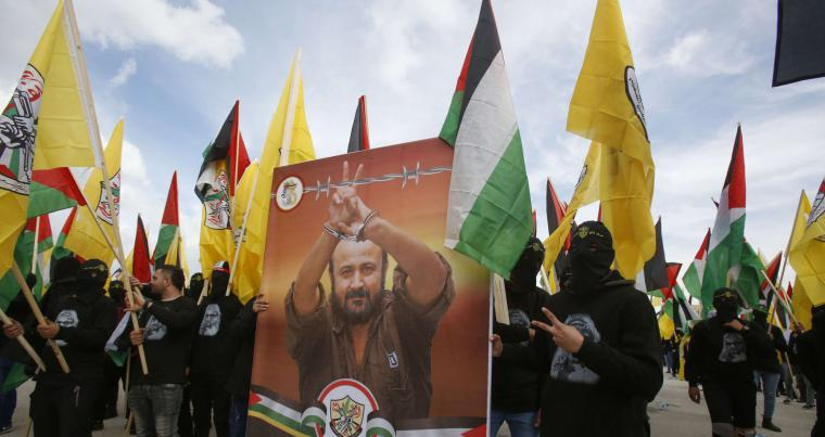 Supporters of the Palestinian Fatah movement march with a poster of imprisoned Fatah leader Marwan Barghouti  in the West Bank town of Bethlehem on January 1, 2020. AFP
