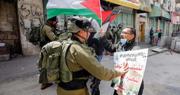 A Palestinian demonstrator argues with an Israeli soldier during a protest against visits by Israeli settlers, in Hebron in the Israeli-occupied West Bank March 31, 2021. (REUTERS)